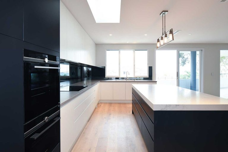 A beautiful new polyurethane kitchen features stone benchtops and contrasting cabinetwork.