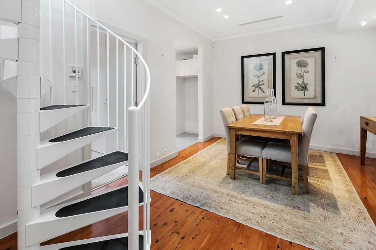 A new steel spiral staircase leads up from the dining area to the former attic in this Mosman terrace, now converted to a lounge space.