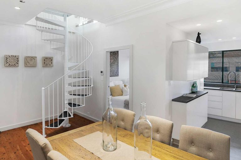 A new steel spiral staircase leads up to the former attic in this Mosman terrace, now converted to an open lounge/reading area.