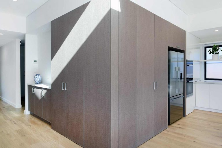 Large pantry cupboards are integrated into the kitchen and hallway of the Naremburn home.