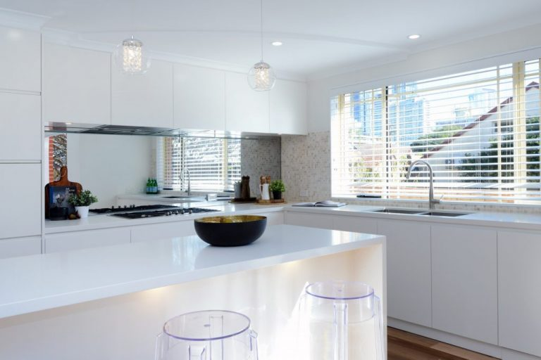 The new kitchen in the Chatswood residence features a waterfall island and contemporary lines with an expansive window view.