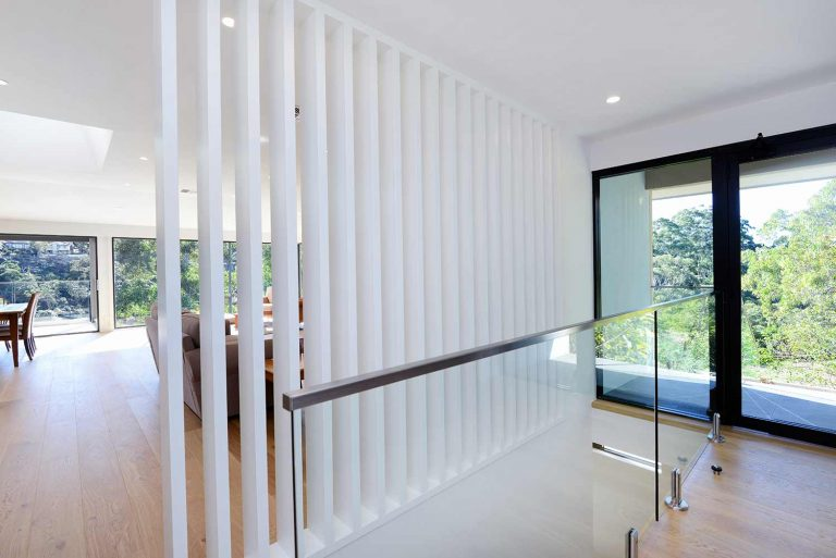 The stairs in the renovated Naremburn home are framed by a white wooden colonnade and glass balustrade.